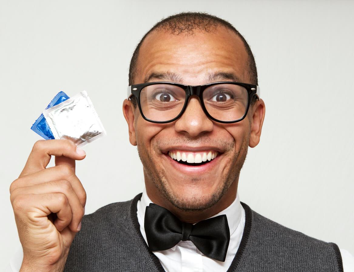 άντρας με γυαλιά κρατά προφυλακτικά ενώ χαμογελά
