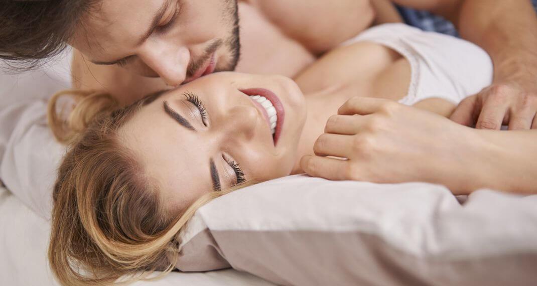άνδρας φιλά γυναίκα στο μάγουλο ξαπλωμένοι στο κρεβάτι