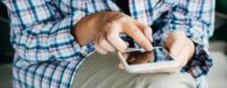 κοπέλα κρατά κινητό τηλέφωνο και στέλνει μήνυμα