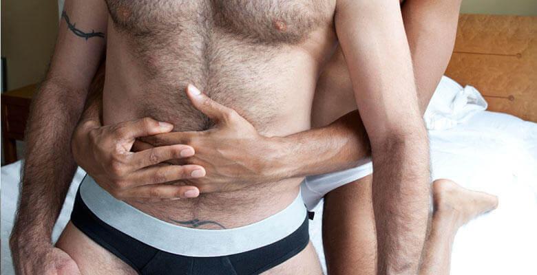 ζευφάρι ανδρών αγκαλιά επάνω σε κρεβάτι