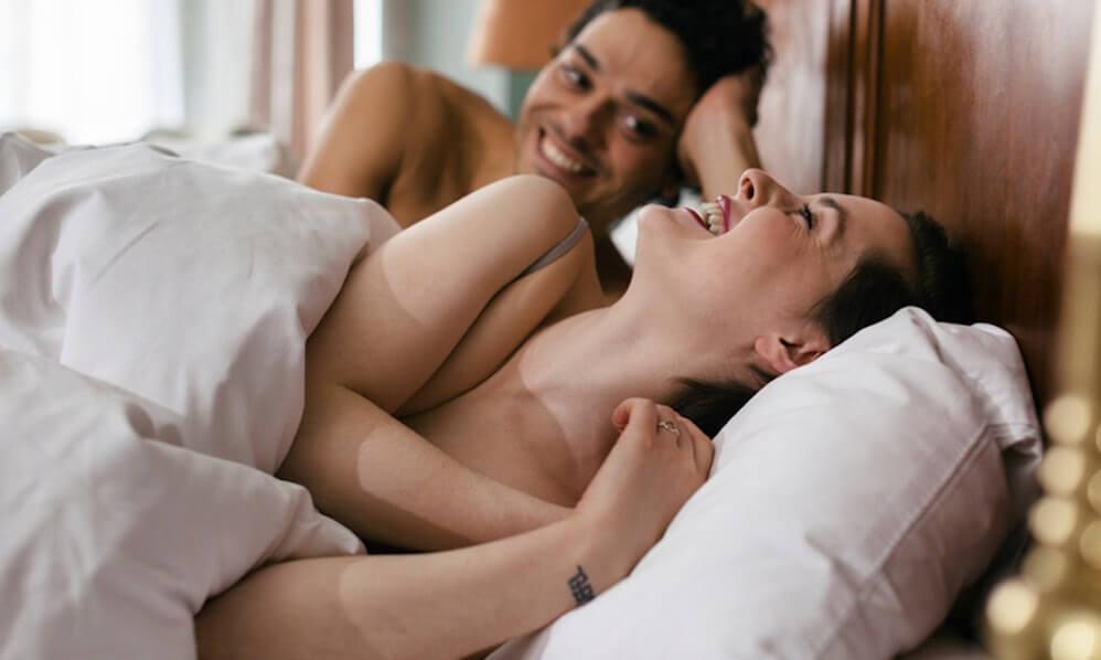 ζευγάρι στο κρεβάτι να χαμογελά με τη γυναίκα σε πρώτο πλάνο